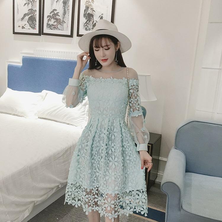 ชุดเดรสลูกไม้ ถักโครเชต์รูปดอกไม้สีฟ้าอมเขียว คอเสื้อ ไหล่ และปลายแขนเสื้อเป็นผ้าโปร่งซีทรู
