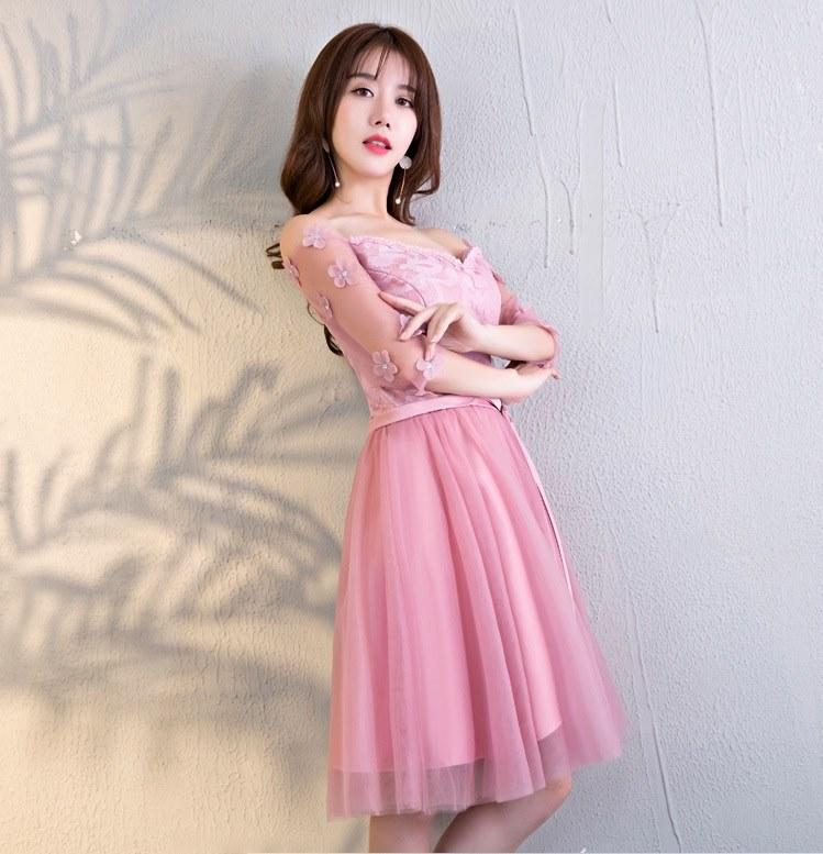 ชุดเดรสออกงาน สุดหรู ตัวเสื้อผ้าลูกไม้ลายดอกไม้สีชมพู เปิดไหล่ แขนยาวสี่ส่วน