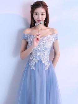 ชุดราตรียาว เปิดไหล่ ปิดต้นแขน ตัวเสื้อด้านนอกสุดเป็นผ้าโปร่งสีฟ้า ซับในชั้นแรกด้วยผ้าลูกไม้สีขาว